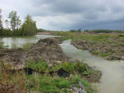 Picture of a large field with deep flooded ruts