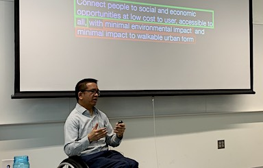 Man sits in wheelchair in front of a screen, presenting research on public transportation